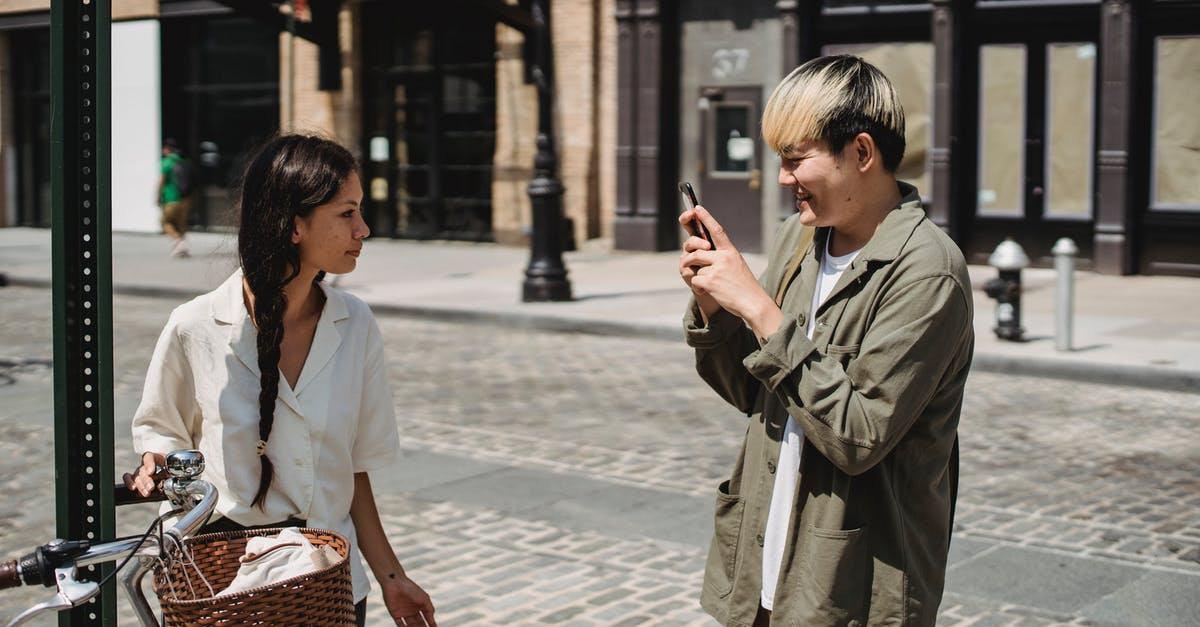 A man and a woman walking down the street talking on a cell phone